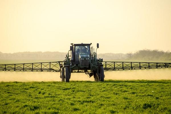 Traktor sprüht Gift auf Pflanzen